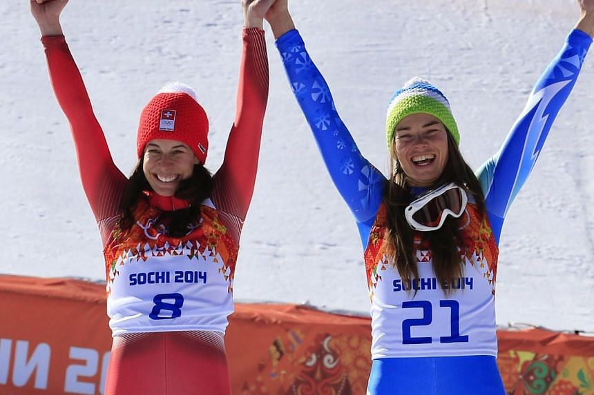 Gold medallists Slovenia's Tina Maze (right) and Switzerland's Dominique Gisin stand on the podium at the Women's Alpine Skiing Downhill Flower Ceremony at the Rosa Khutor Alpine Center during the Sochi Winter Olympics, on Feb 12, 2014. Switzerland's
