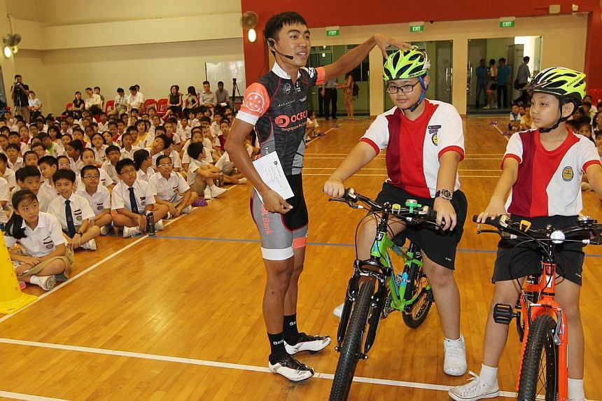 Two professional cyclists from OCBC Singapore Professional Cycling Team including Low Ji Wen (left) , 24, speaks to about 800 primary school students in Yu Neng Primary including Ryan Muhd Syafiq (centre), 12, and Jovi Huang (right), 12, to give them