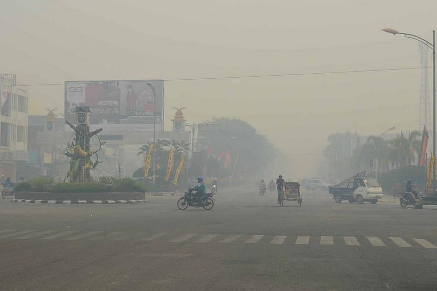 Traffic shrouded in haze on the outskirts of Dumai on Feb 11, 2014. The number of hot spots in Sumatra more than doubled to over 450 on Feb 11, from about 190 a day earlier.The likelihood of transboundary haze hitting Singapore is low so far as