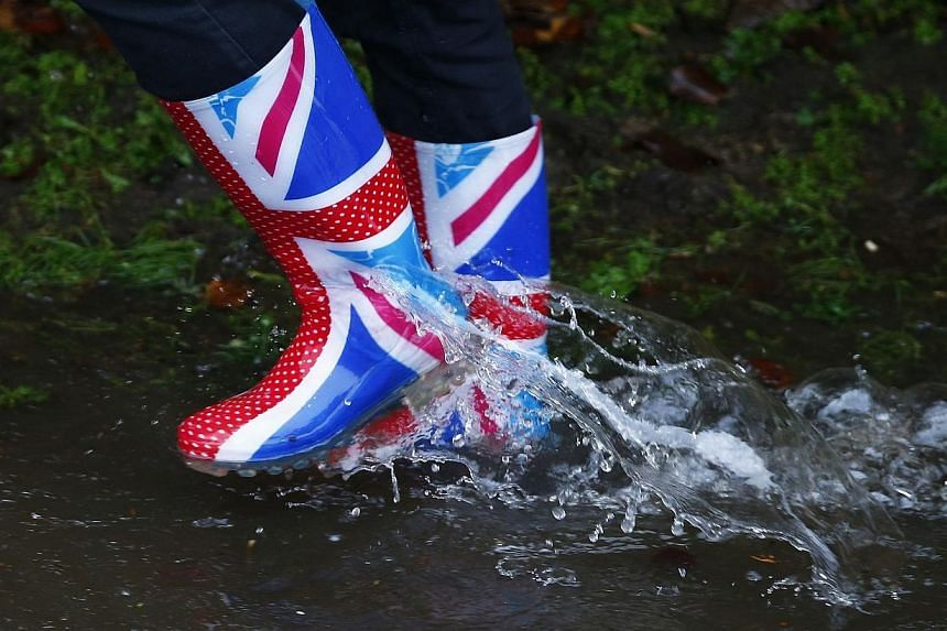 A resident's Wellington boots are seen splashing through water after the river Thames flooded the village of Wraysbury, southern England, on Feb 11, 2014. -- PHOTO: REUTERS