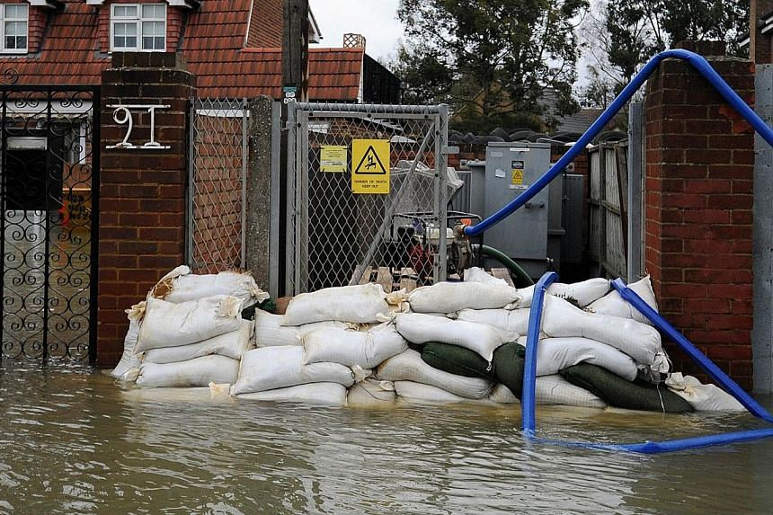 Sandbags protect a an electricity sub-station as flooding continues in Staines, west of London, on Feb 12, 2014. -- PHOTO: AFP
