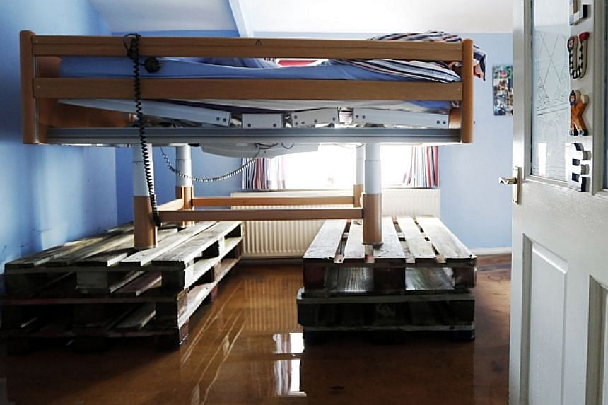 A specialist electric bed for a disabled boy is raised on pallets to try and protect it from flood water in a home at Burrowbridge in south west England, on Feb 9, 2014. -- FILE PHOTO: REUTERS