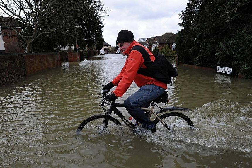 A man cycles on a flooded road in Staines, west of London, on Feb 12, 2014. -- PHOTO: AFP