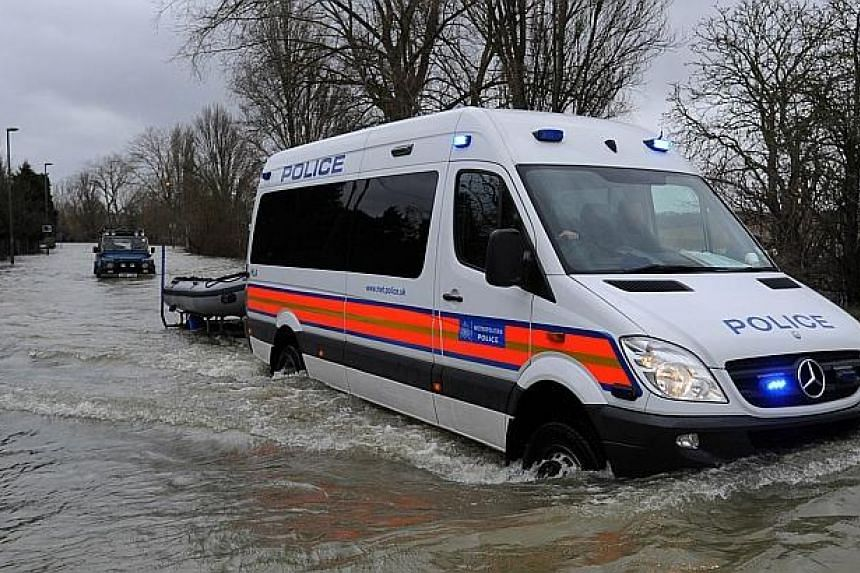A police van towing a boat drives along a flooded road in Staines, west of London, on Feb 12, 2014. -- PHOTO: AFP