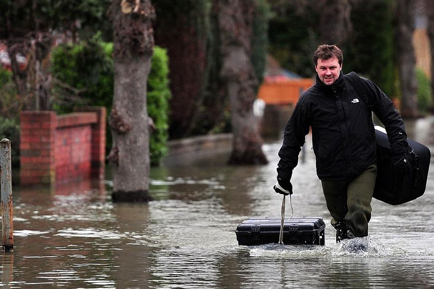A man drags his possessions in a peli-case as he wades along a flooded road near Staines, west of London, on Feb 12, 2014. -- PHOTO: AFP