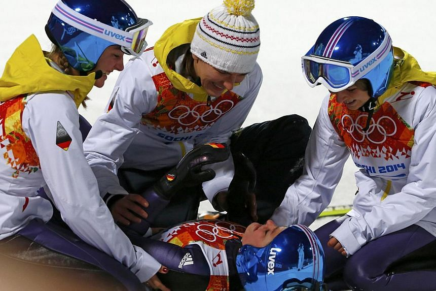 Winner Germany's Carina Vogt (centre), lies on the ground as she celebrates with team mates after her victory in the women's ski jumping individual normal hill event of the Sochi 2014 Winter Olympic Games, at the RusSki Gorki Ski Jumping Center in Ro