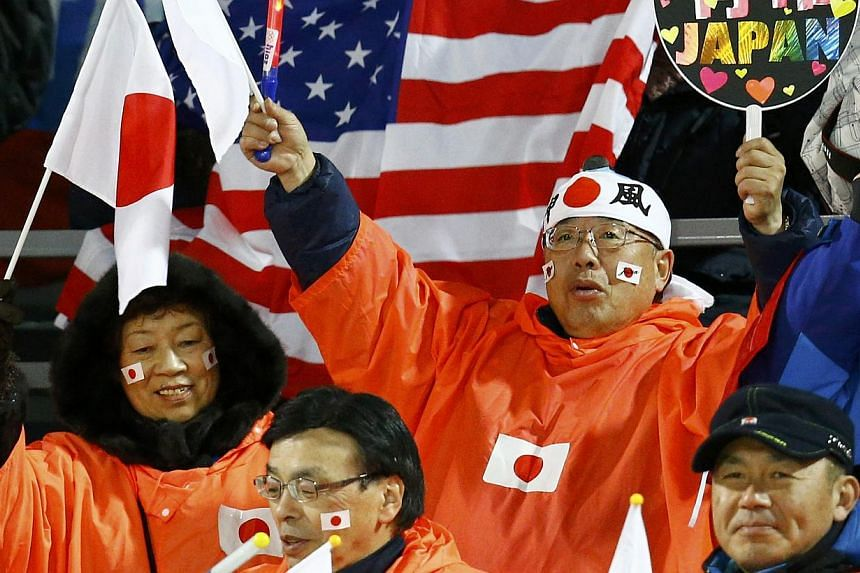 A fan of Japan cheers during the first round of the women's ski jumping individual normal hill event at the Sochi 2014 Winter Olympic Games, at the RusSki Gorki Jumping Centre, in Rosa Khutor on Feb 11, 2014. -- PHOTO: REUTERS