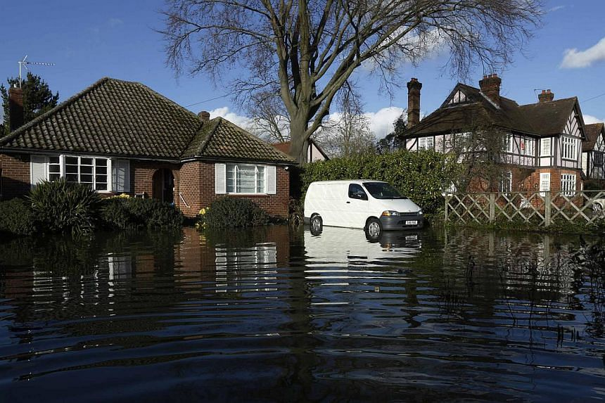 Homes and vehicles are surrounded by flood water after the river Thames flooded the village of Wraysbury, southern England on Feb 11, 2014. Prime Minister David Cameron warned on Tuesday that the British floods were likely going to get worse before t