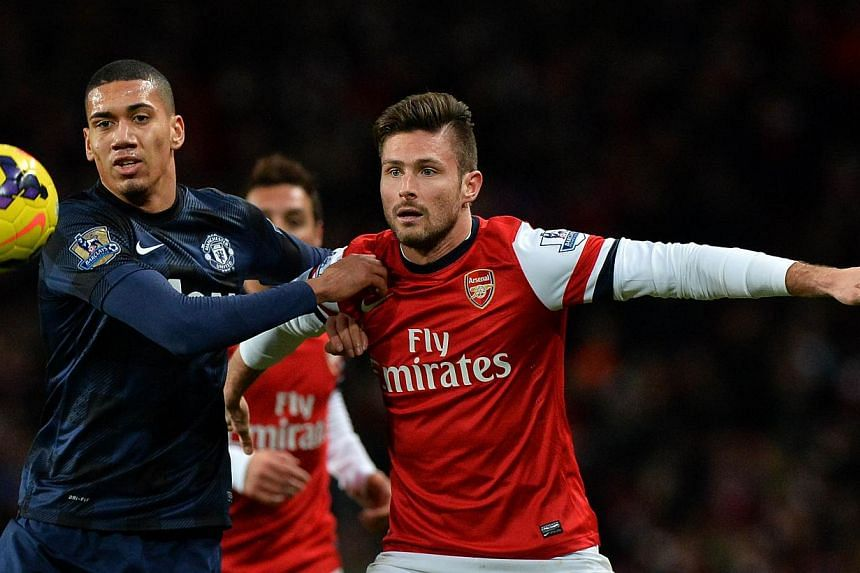 Manchester United's English defender Chris Smalling (left) vies for the ball with Arsenal's French striker Olivier Giroud during the English Premier League football match between Arsenal and Manchester United at the Emirates Stadium in London, on Feb
