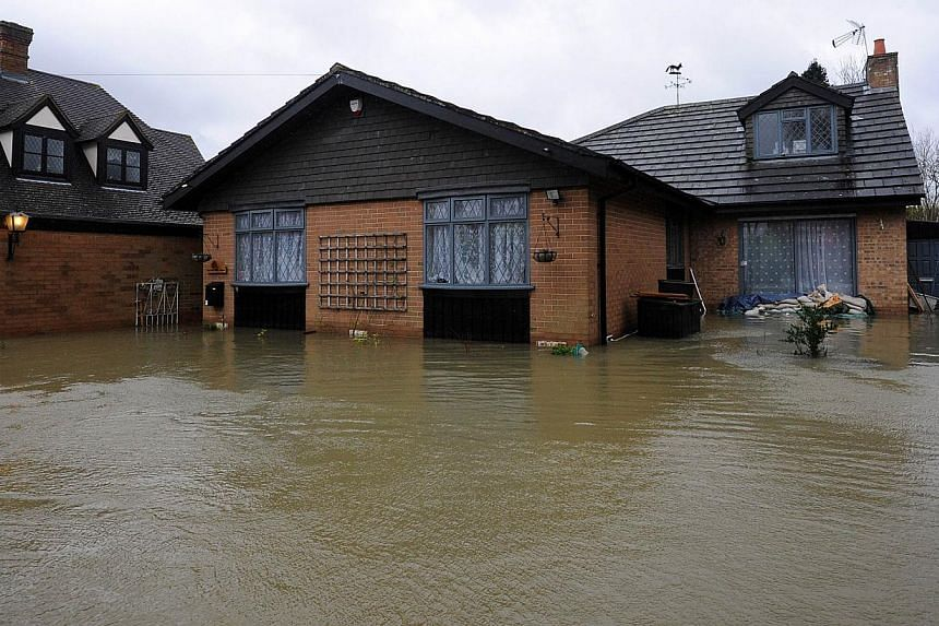 Floodwater surrounds a property in the village of Wraysbury, west of London, on Feb 12, 2014. Flood-hit Britain suffered a fresh battering on Wednesday from storms and high winds that caused power outages to nearly 150,000 homes, the cancellation of