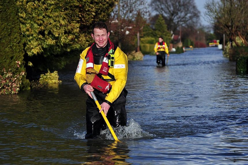 Fire and rescue service personnel wade through floodwater in the village of Wraysbury, west of London, on Feb 12, 2014. -- PHOTO: AFP