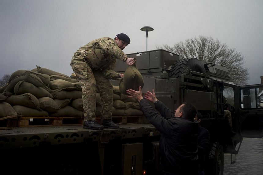 Army sandbags are unloaded to a local shopkeeper in the flooded central square in the village of Datchet in Berkshire, southern England, on Feb 12, 2014. -- PHOTO: REUTERS