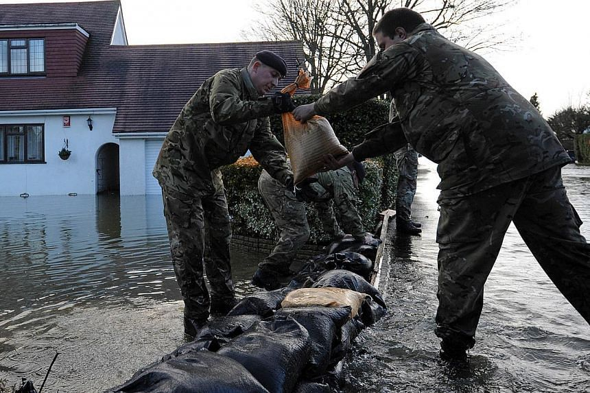 British soldiers build sandbag flood defences in the village of Wraysbury, west of London, on Feb 12, 2014. -- PHOTO: AFP