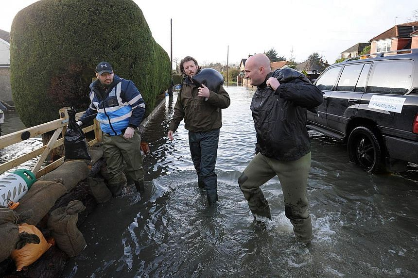 Residents carry sandbags in the flooded village of Wraysbury, west of London, on Feb 12, 2014. -- PHOTO: AFP