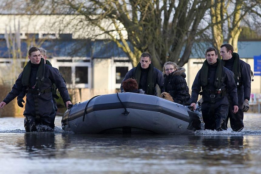 Soldiers transport people in a boat along a flooded street in Egham on Feb 12, 2014. -- PHOTO: AFP