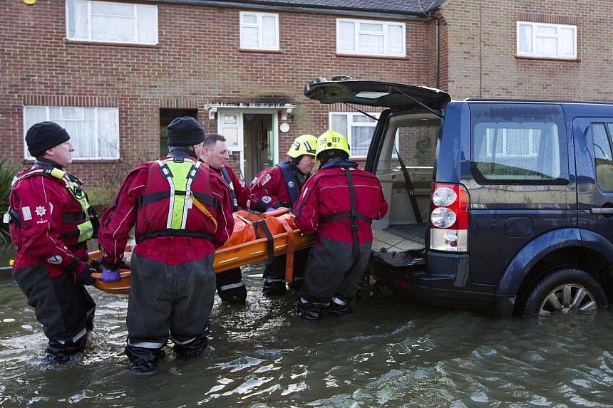 An elderly man is evacuated from his home by fire and rescue services personnel on a flooded street in Egham on Feb 12, 2014. -- PHOTO: AFP
