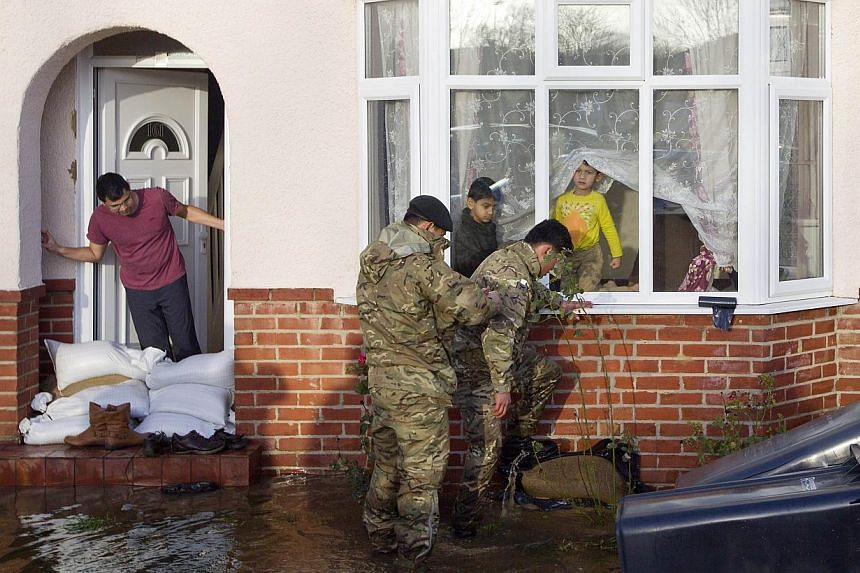 Soldiers assist residents trying to protect their property from floodwaters in Egham, west of London, on Feb 12, 2014. -- PHOTO: AFP