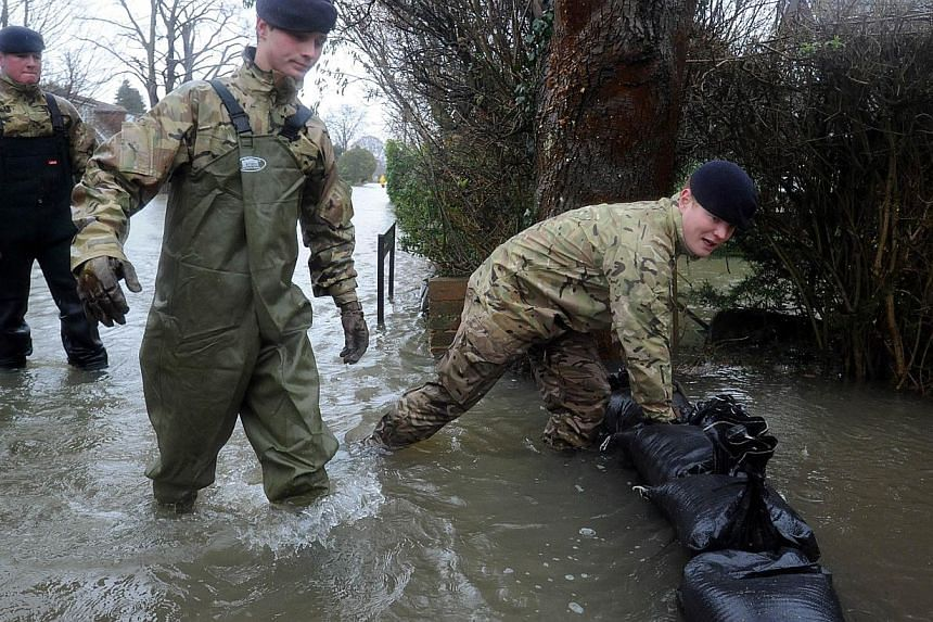 Soldiers attempt to protect a flood-affected property with sandbags in Wraysbury, west of London, on Feb 12, 2014. -- PHOTO: AFP