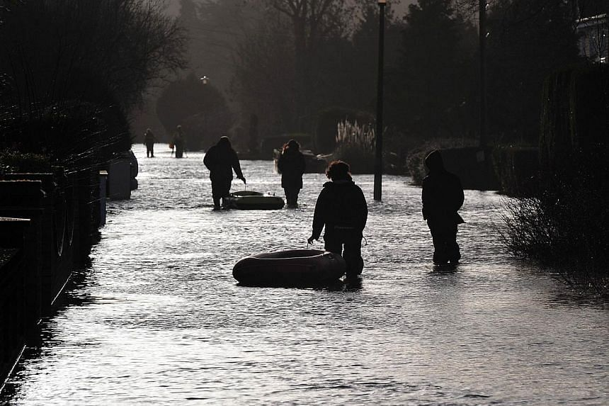 People walk along a flooded road in Wraysbury, west of London, on Feb 12, 2014. -- PHOTO: AFP