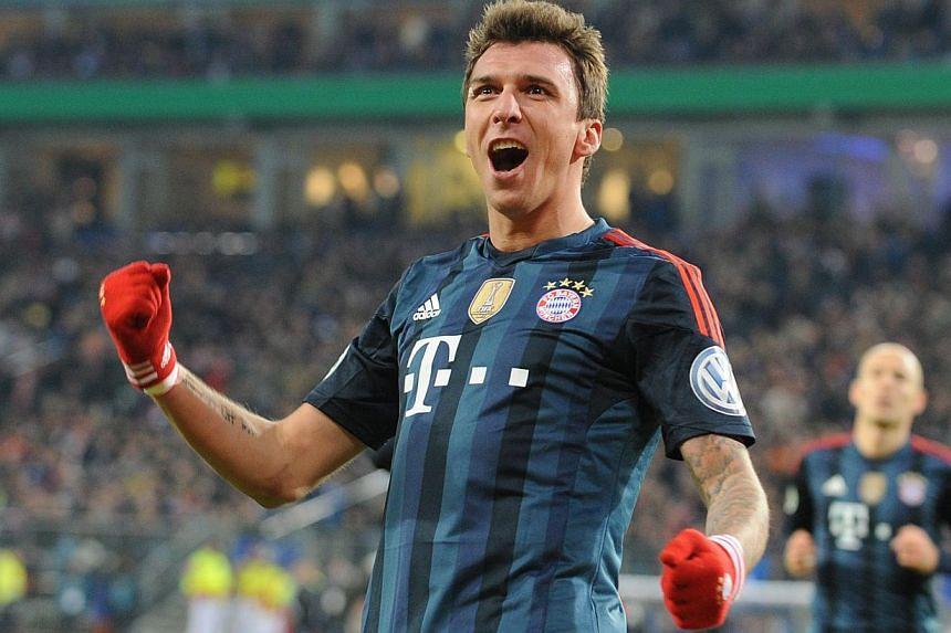 Bayern Munich's Croatian striker Mario Mandzukic celebrates scoring during the German Cup quarter-final football match between Hamburg and Bayern in northern Germany on Feb 12, 2014. Bayern Munich eased their way into the German Cup semi-finals with