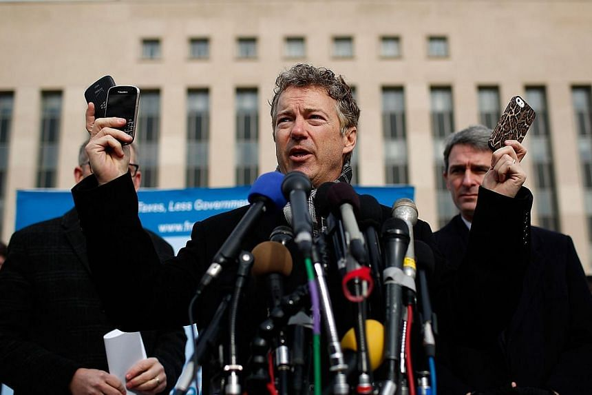 US Senator Rand Paul (R-KY) holds up a group of cell phones in front of US District Court to announce the filing of a class action lawsuit against the administration of US President Obama, Director of National Intelligence James Clapper, NSA Director