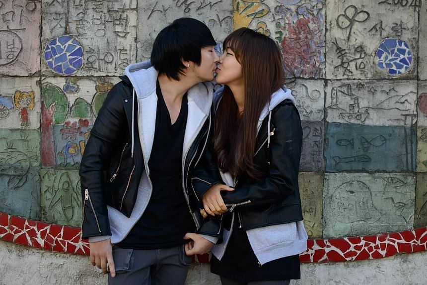 Couple Baek Eun-Joo (right) and Lee Sang-Jun who run Ggumddakji, an online shopping mall specialising in couples clothing, kiss as they pose for a photo near their office in Seoul on Feb 11, 2014. Young South Korean couples often advertise their rela