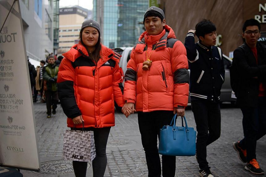 A couple wearing matching clothes pose for a photo at a popular shopping area in Seoul on Feb 9, 2014. Young South Korean couples often advertise their relationship by wearing matching outfits, whether socks, shirts, jackets or, more privately, under