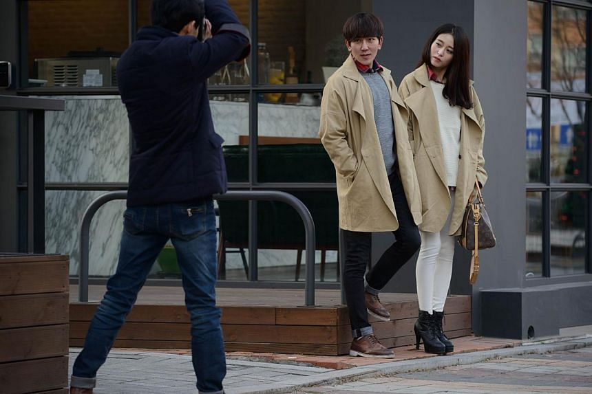 Sun Mun Sung (left) who runs Sweetcat, an online shopping mall specialising in couples clothing, takes photos of models Kim Hun Jung (right) and An Tae Hyun (centre) during a photo shoot on the outskirts of Seoul on Feb 12, 2014. Young South Korean c