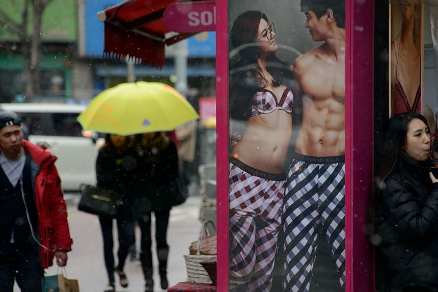 A poster advertises matching pyjamas for couples at a popular shopping area in Seoul on Feb 9, 2014. Young South Korean couples often advertise their relationship by wearing matching outfits, whether socks, shirts, jackets or, more privately, underwe