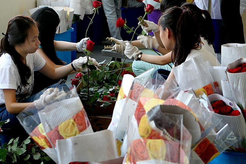 Xpressflower.com employees packing blooms for Valentine's Day at the florist's Paya Lebar outlet.-- ST PHOTOS: LAU FOOK KONG