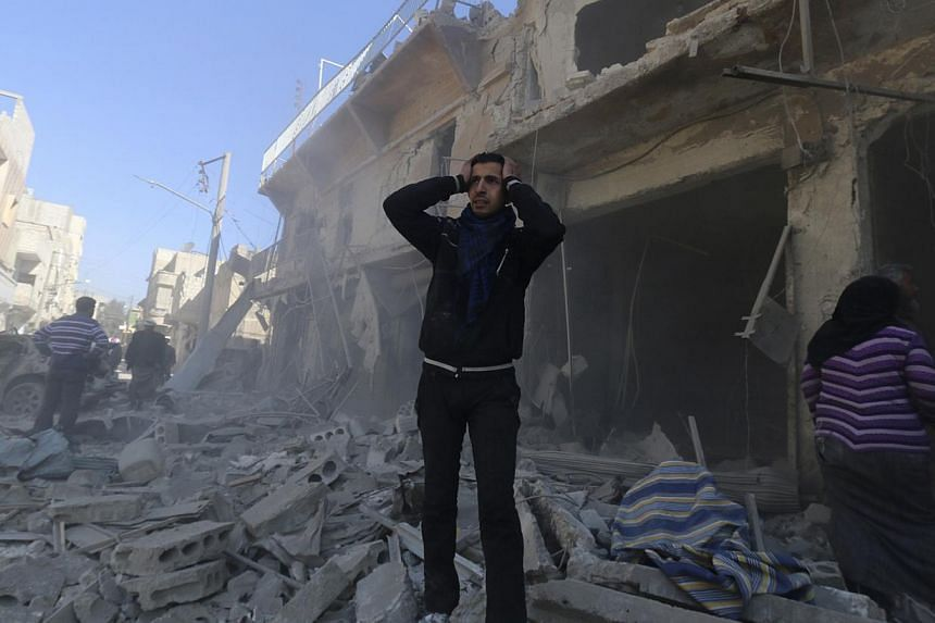 A man reacts at a site hit by what activists said were explosive barrels thrown by forces loyal to Syria's President Bashar al-Assad in the Al-Haidariya neighbourhood of Aleppo, on Feb 12, 2014. More Syrians have been killed in the three weeks since