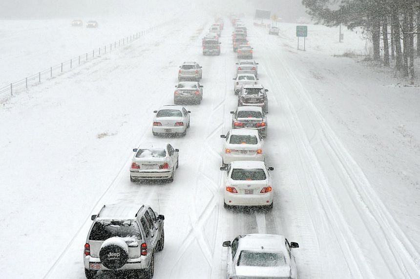 Traffic along Edwards Mill Road moves slowly in Raleigh, North Carolina, on Feb 12, 2014. Motorists were encouraged to stay off roads after Gov Pat McCrory declared a state of emergency on Wednesday, ahead of the winter storm. -- PHOTO: AFP