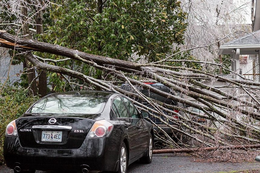 A broken tree limb rests on a parked home after a rare winter storm coated most of the South with ice in Summerville, South Carolina, on Feb 12, 2014. -- PHOTO: AFP