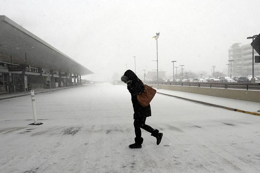 A pedestrian braces against the wind and snow on her way into Raleigh-Durham International Airport in Morrisville, North Carolina, on Feb 12, 2014. -- PHOTO: AFP