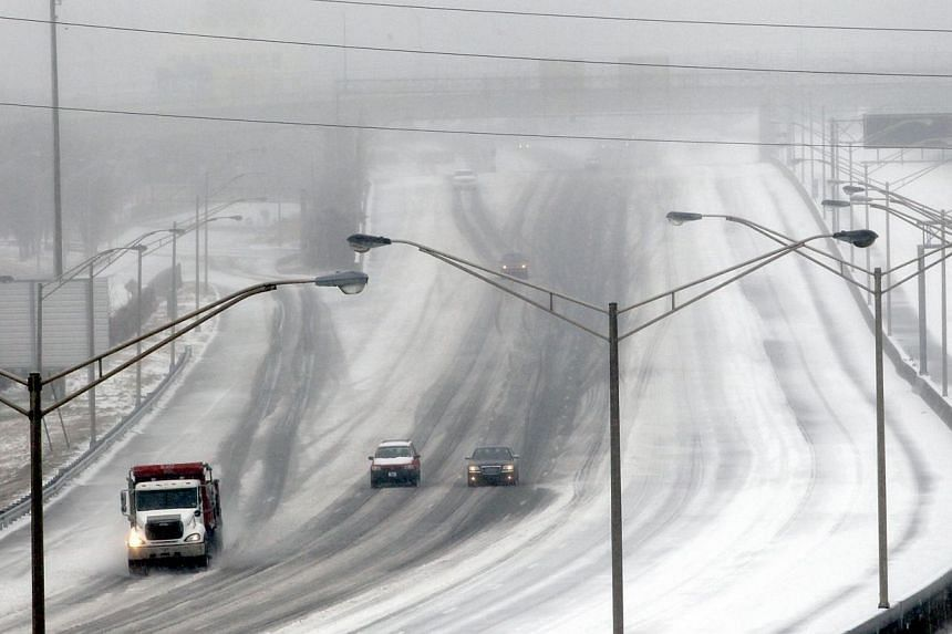 A sand truck dumps salt and sand on a downtown expressway as drivers follow behind during an ice storm in Atlanta, Georgia, Feb 12, 2014. -- PHOTO: REUTERS
