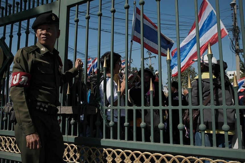 A security guard stands behind a gate as Thai anti-government protesters wave national flags outside the customs department in Bangkok on January 14, 2014. Thousands of Thai opposition protesters marched on government buildings in the capital as part