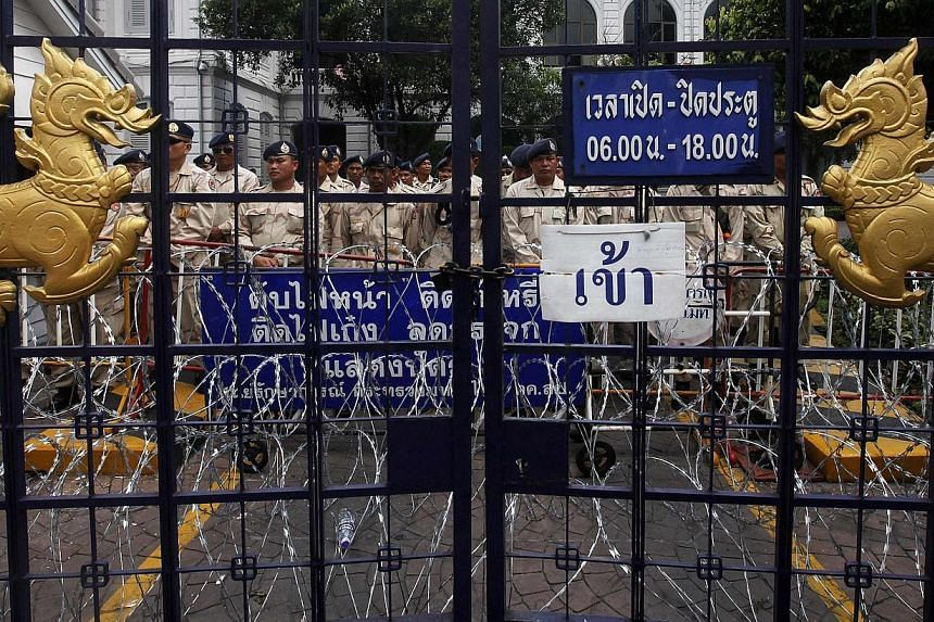 Security personnel stand behind one of the gates of Thailand's Interior Ministry as anti-government protesters gather outside in Bangkok on November 26, 2013. -- PHOTO: REUTERS