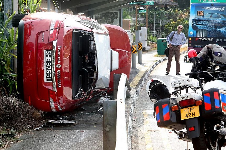 About 7.30am this morning, Feb 13, 2014,a taxi rammed into rail and landed on the pavement near the bus stop at Serangoon way towards the junction of Yio Chu Kang. -- ST PHOTO:LAU FOOK KONG
