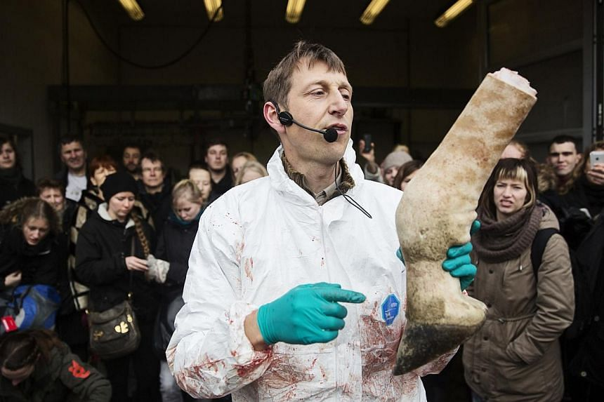 People look on as a veterinarian holds a leg of the giraffe Marius while it was being dismembered in Copenhagen Zoo, Feb 9, 2014. -- FILE PHOTO: REUTERS