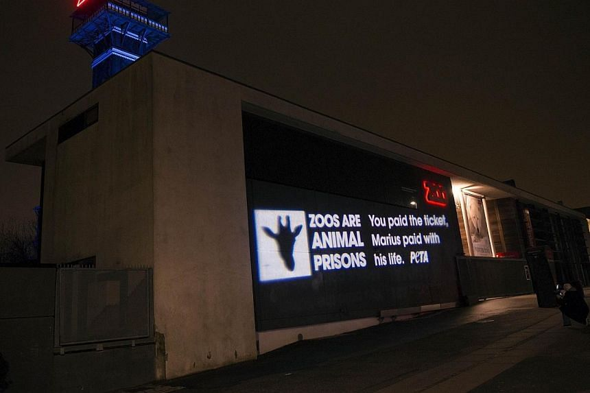 """German light artist Oliver Bienkowski projects a message reading """"Zoos are animal prisons,You paid the ticket, Marius paid with his life. Peta."""" on the entrance of the Copenhagen Zoo for the animal activist group Peta on Feb 11, 2014. -- PHOTO: AFP"""