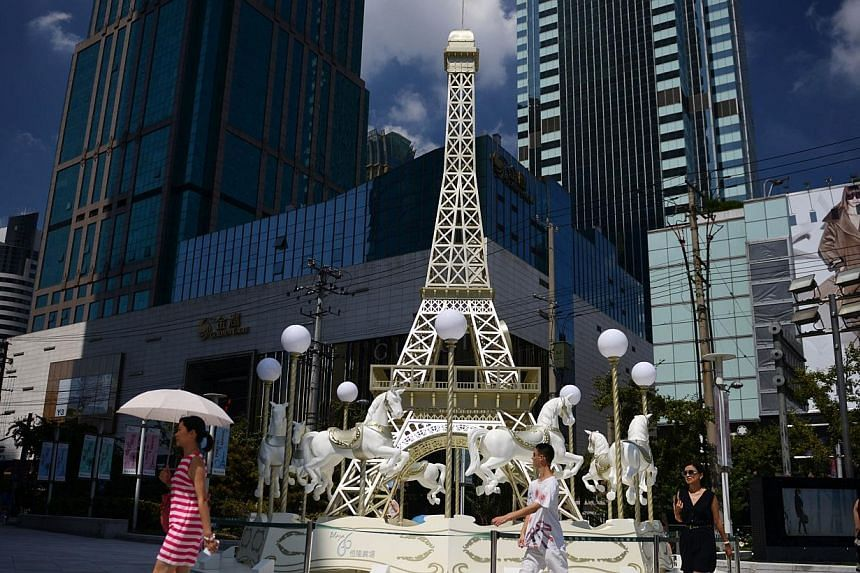 A merry-go-round modeled on Paris' Eiffel Tower is seen outside an upmarket shopping mall in Shanghai on Aug 13, 2013. Couples looking to enjoy a romantic Valentine's Day at one Chinese cinema will be out of luck this Friday, Feb 14, 2014, thwar