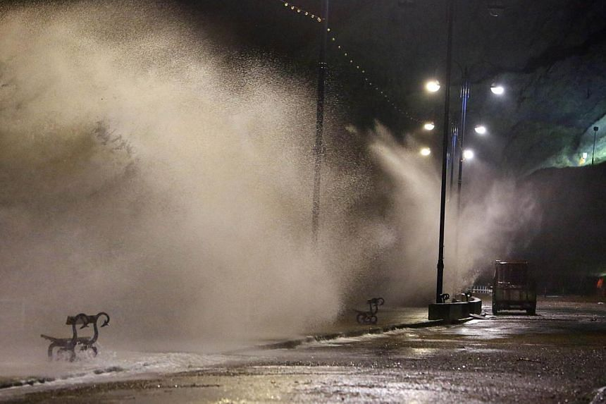 Waves break over the sea wall at high tide at Aberystwyth, west Wales, on Feb 12, 2014, as a storm strikes the west of Britain with winds gusting at up to 160kmh in some places. A man in his 70s died in a suspected electrocution after a tree brought