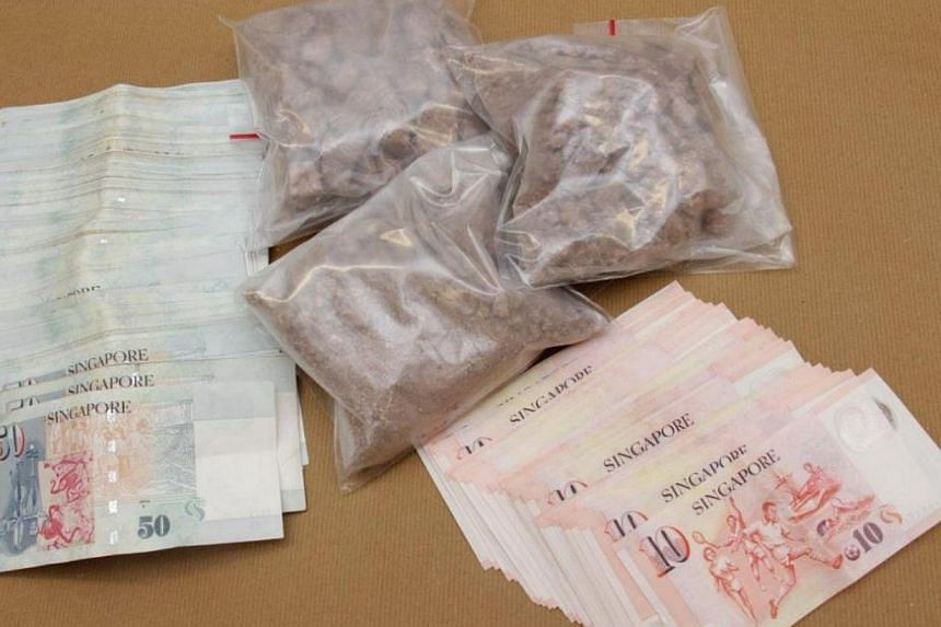 Heroin and cash seized in a CNB operation at Paya Lebar, on Feb 12, 2014. -- PHOTO: CENTRAL NARCOTICS BUREAU