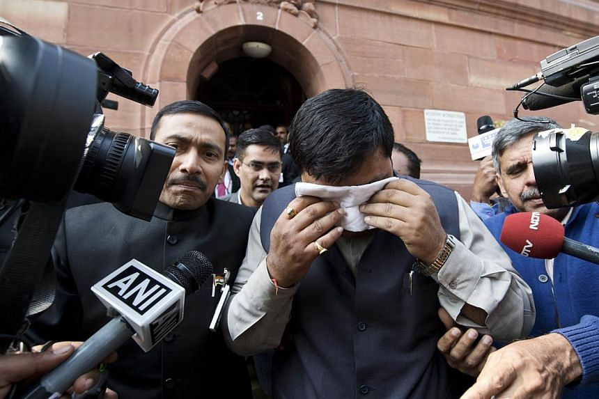 An unidentified member of India's Parliament, holding a handkerchief to his face after being affected by pepper spray, leaves Parliament after protests inside the building in New Delhi, on Feb 13, 2014. India's parliament erupted in mayhem on Thursda