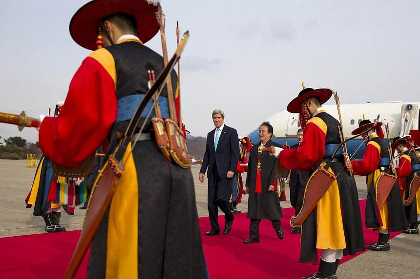 US Secretary of State John Kerry (centre left) walks with US Ambassador to South Korea Sung Kim past an honor guard after arriving at Seoul Air Base, on Feb 13, 2014. US Secretary of State John Kerry arrived in Seoul on Thursday, Feb 13, 2014, for di