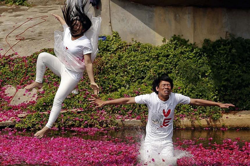 Groom Praem Pam Srichamnan and his bride Suriya Utai jump into a pond during a wedding ceremony ahead of Valentine´s Day in Prachin Buri province, east of Bangkok, Feb 13, 2014. Three Thai couples took part in the wedding ceremony arranged by a reso