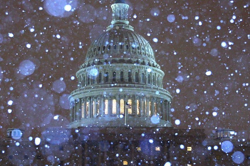 Snow falls in front of the US Capitol building on Feb 13, 2014 in Washington, DC. A deadly and intensifying winter storm packing heavy snow, sleet and rain pelted a huge swath of the US East Coast on Thursday, Feb 13, 2014, grounding flights and shut