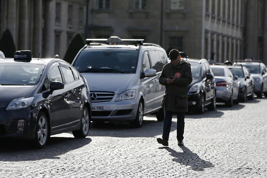 Taxi drivers on strike stand near the Eiffel tower as they protest in Paris on Feb 10, 2014. Paris taxi drivers vowed Wednesday to push on with strikes that caused logjams on city streets and at airports, despite the damage done to their already ques
