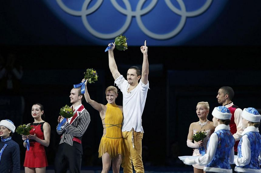 First-placed Russia's Tatiana Volosozhar (centre,left) and Maxim Trankov celebrate on the podium, next to second-placed Russia's Ksenia Stolbova (left) and Fedor Klimov (second left) and third-placed Germany's Aliona Savchenko and Robin Szolkowy (rig