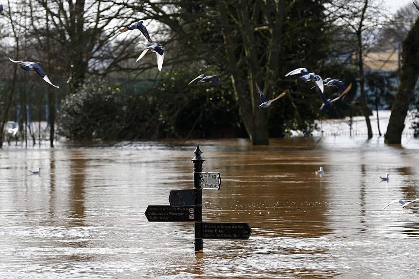Birds fly past a sign surrounded by flood waters in Worester, central England, on Feb 13, 2014.Tens of thousands of Britons endured a second day without power on Thursday as yet another Atlantic storm barrelled towards a country struggling to d